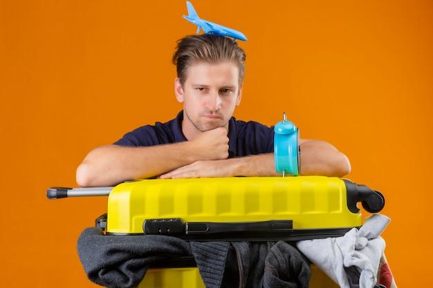 Junger hübscher reisender mann, der mit koffer voll von kleidern mit wecker und mit spielzeugflugzeug auf seinem kopf steht und müde und gelangweilt mit traurigem ausdruck auf gesicht über orange hintergrund schaut
