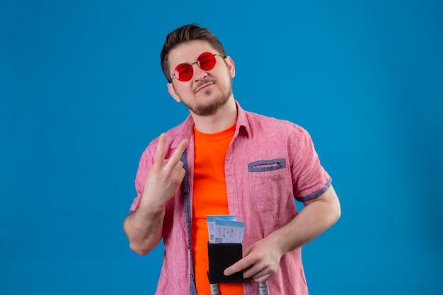 Junger hübscher reisender mann, der sonnenbrillen hält, die flugtickets halten, die zuversichtlich suchen, nummer zwei stehend über blauer wand zu zeigen