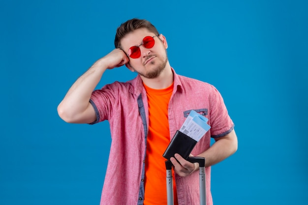 Junger hübscher reisender mann, der sonnenbrillen hält, die flugtickets mit traurigem ausdruck auf gesicht stehen, das über blauer wand steht