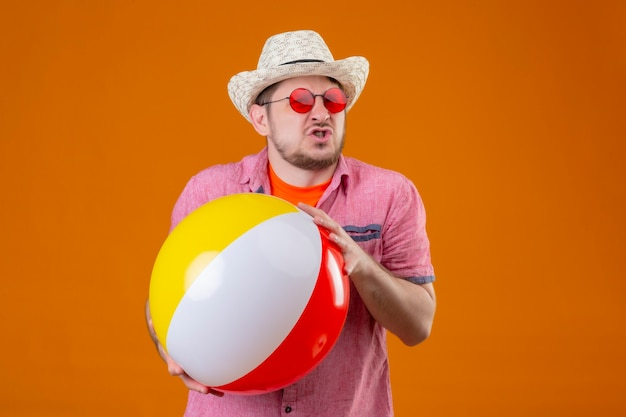 Junger hübscher reisender mann im sommerhut, der aufblasbaren ball hält, der sich gereizt fühlt