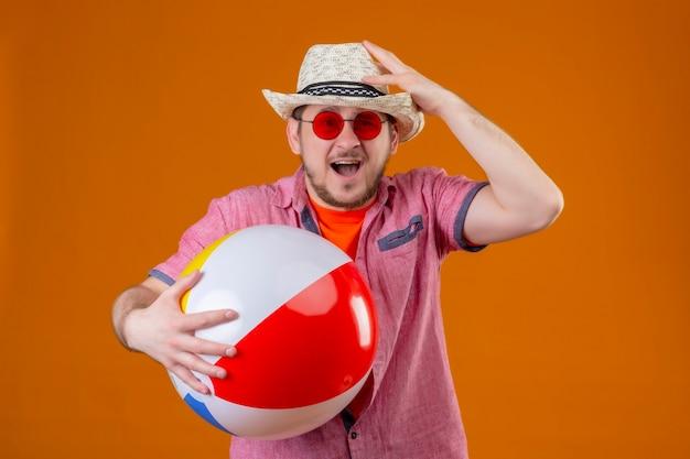 Junger hübscher reisender mann im sommerhut, der aufblasbaren ball hält