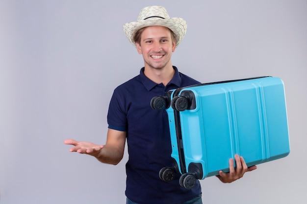 Junger hübscher reisender mann im sommerhut, der koffer hält, der fröhlich kamera betrachtet, die mit arm steht, der über weißem hintergrund angehoben wird