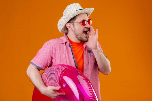 Junger hübscher reisender mann im sommerhut mit aufblasbarem ringschreien