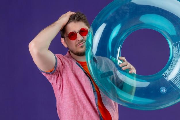 Junger hübscher reisender mann mit aufblasbarem ring mit hand auf kopf für fehler