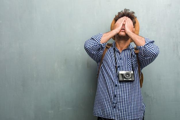 Junger hübscher reisendmann, der einen strohhut, einen rucksack und eine fotokamera frustriert und hoffnungslos trägt