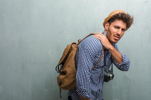 Junger hübscher reisendmann, der einen strohhut, einen rucksack und eine fotokamera mit den rückseitigen schmerz wegen des arbeitsdruckes, müde und klug trägt