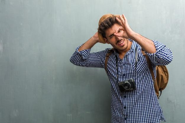 Junger hübscher reisendmann, der einen strohhut, einen rucksack und eine fotokamera nett und überzeugt trägt, okaygeste tuend, aufgeregt und schreiend, konzept der zustimmung und erfolg