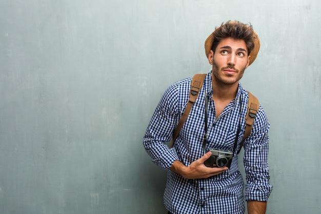 Junger hübscher reisendmann, der einen strohhut, einen rucksack und eine fotokamera oben schauen trägt