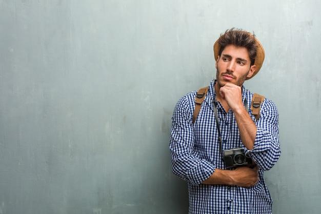 Junger hübscher reisendmann, der einen strohhut, einen rucksack und eine fotokamera trägt