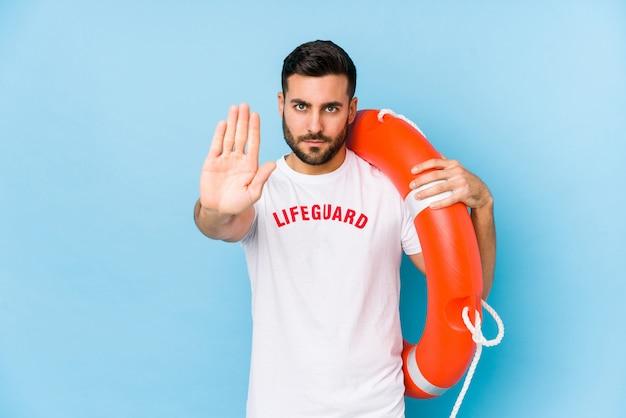 Junger hübscher rettungsschwimmermann, der mit ausgestreckter hand steht, die stoppschild zeigt