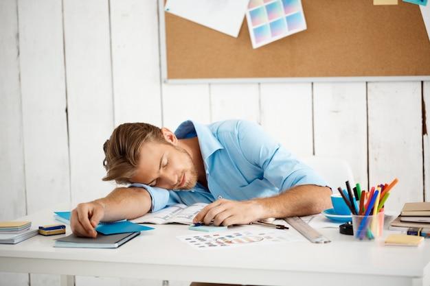 Junger hübscher schläfriger müder geschäftsmann, der am tisch auf papieren und notizblock schläft. weiße moderne büroeinrichtung