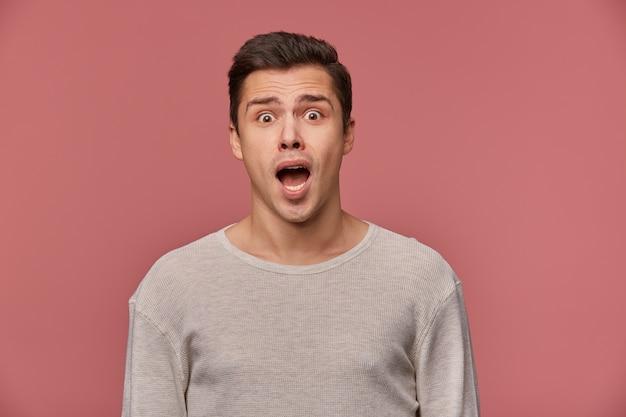 Junger hübscher schockierter mann im leeren langen ärmel, schaut auf die kamera mit mit weit offenem mund in überraschtem ausdruck, lokalisiert über rosa hintergrund.