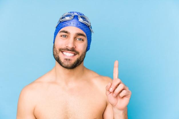 Junger hübscher schwimmermann isoliert, der nummer eins mit finger zeigt.
