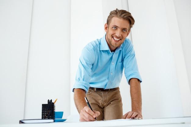 Junger hübscher, selbstbewusster, fröhlicher geschäftsmann, der am tisch steht und skizze zeichnet. lächelnd. weiße moderne büroeinrichtung