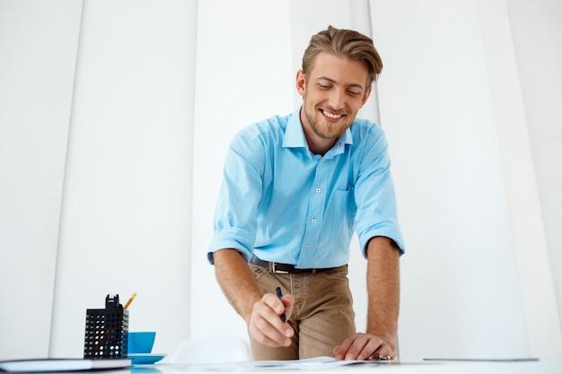 Junger hübscher, selbstbewusster, fröhlicher, lächelnder geschäftsmann, der am tisch steht und skizze zeichnet. weiße moderne büroeinrichtung