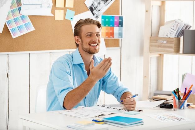 Junger hübscher selbstbewusster lächelnder geschäftsmann, der am tisch sitzt. weiße moderne büroeinrichtung
