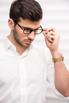 Junger hübscher selbstbewusster mann mit gläsern.