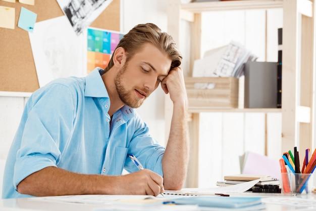 Junger hübscher selbstbewusster nachdenklicher geschäftsmann, der am tisch sitzt, der im notizblock schreibt. weiße moderne büroeinrichtung