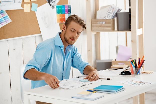 Junger hübscher selbstbewusster nachdenklicher geschäftsmann, der am tisch sitzt und durch papiere schaut. weiße moderne büroeinrichtung
