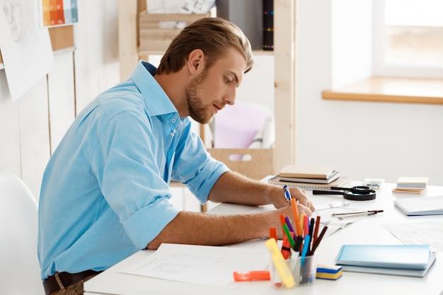 Junger hübscher selbstbewusster nachdenklicher geschäftsmann, der am tisch sitzt und in notizbuch schreibt. weiße moderne büroeinrichtung
