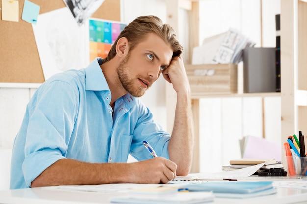 Junger hübscher, selbstbewusster, nachdenklicher geschäftsmann, der am tisch sitzt und über notizblock nachdenkt. weiße moderne büroeinrichtung