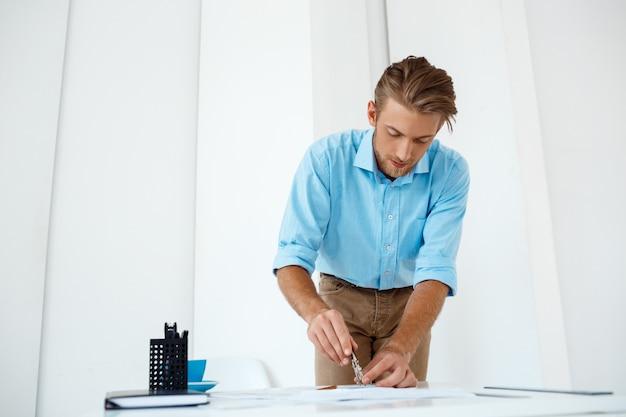 Junger hübscher selbstbewusster nachdenklicher geschäftsmann, der an der tischzeichnungsskizze stehend arbeitet. . weiße moderne büroeinrichtung