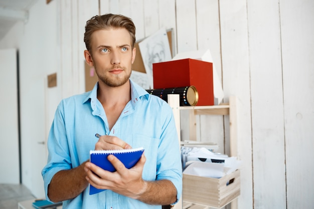 Junger hübscher selbstbewusster nachdenklicher geschäftsmann, der in notizbuch schreibt. weiße moderne büroeinrichtung