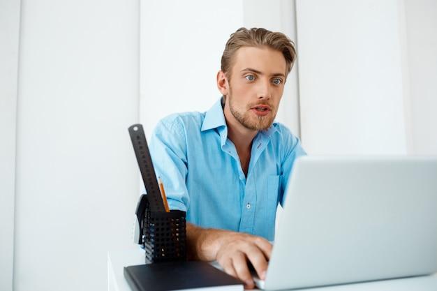 Junger hübscher, selbstbewusster, überraschter geschäftsmann, der am tisch sitzt und an laptop mit tasse kaffee beiseite arbeitet. weiße moderne büroeinrichtung