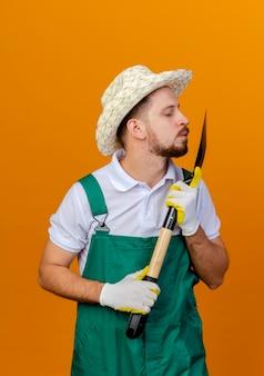 Junger hübscher slawischer gärtner in der uniform, die hut und gartenhandschuhe trägt und spaten hält und kussgeste lokalisiert auf orange wand hält