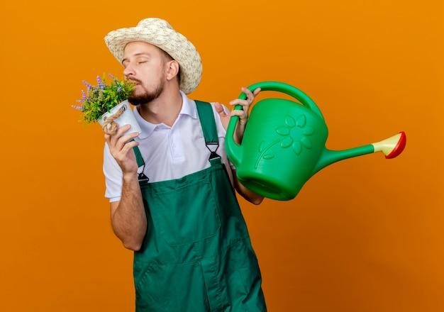 Junger hübscher slawischer gärtner in uniform und hut, der blumentopf und bewässerung hält, kann blumen mit geschlossenen augen schnüffeln, die auf orange wand lokalisiert werden