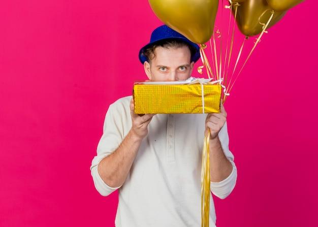 Junger hübscher slawischer partei-kerl, der parteihut hält, der ballons und geschenkbox hält, die kamera von hinter geschenkbox lokalisiert auf purpurrotem hintergrund mit kopienraum betrachtet