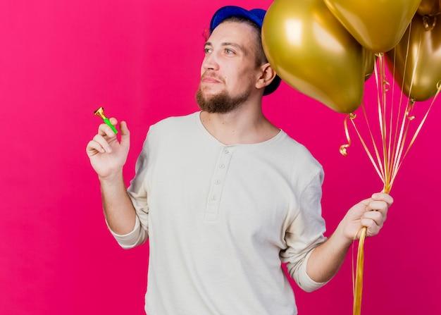 Junger hübscher slawischer party-typ, der partyhut hält, der ballons und partygebläse hält, die seite lokalisiert auf rosa wand betrachten