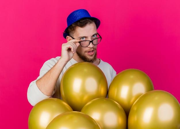 Junger hübscher slawischer party-typ, der partyhut und brille trägt, die hinter ballons stehen, die gläser betrachten, die front lokalisiert auf rosa wand betrachten