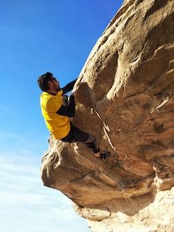 Junger hübscher sportler, der auf eine felsenklippe klettert