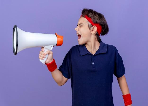 Junger hübscher sportlicher junge, der stirnband und armbänder mit zahnspangen trägt, die kopf zur seite drehen und in lautsprecher mit geschlossenen augen schreien, die auf lila wand lokalisiert werden