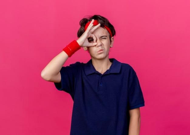 Junger hübscher sportlicher junge, der stirnband und armbänder mit zahnspangen trägt, die vorne zwinkern und blickgeste lokalisiert auf rosa wand tun