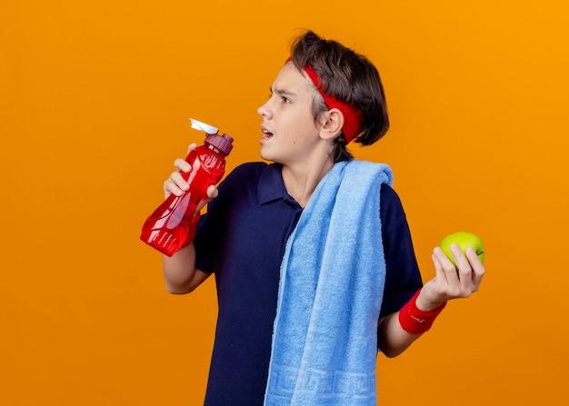 Junger hübscher sportlicher junge, der stirnband und armbänder mit zahnspangen und handtuch auf der schulter trägt, die kopf zur seite dreht und apfel- und wasserflasche lokalisiert auf orange wand mit kopienraum hält