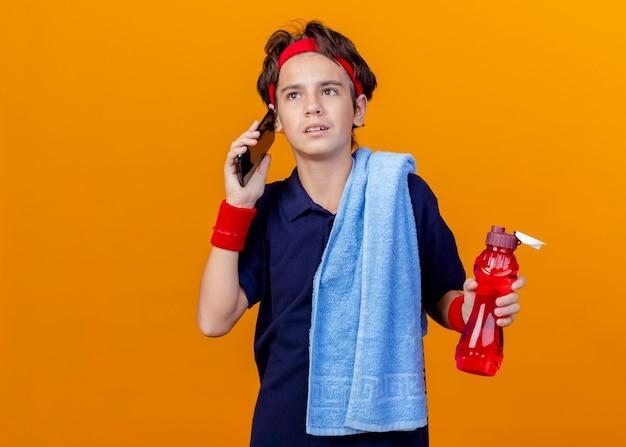 Junger hübscher sportlicher junge, der stirnband und armbänder mit zahnspangen und handtuch auf schulter hält wasserflasche hält, die am telefon lokalisiert auf orange wand mit kopienraum hält