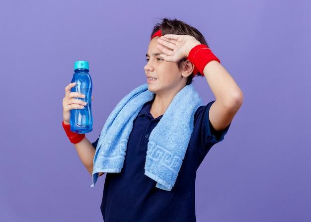 Junger hübscher sportlicher junge, der stirnband und armbänder mit zahnspangen und handtuch um den hals lokalisiert auf lila wand trägt