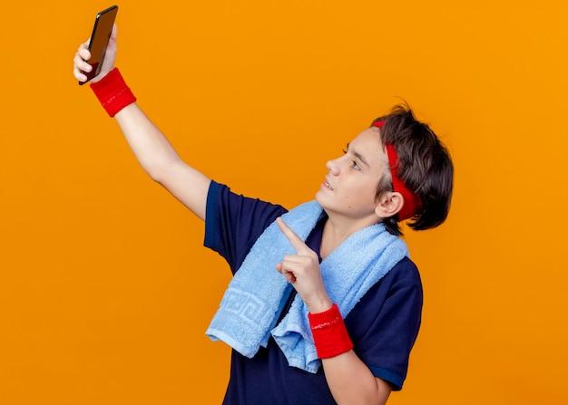 Junger hübscher sportlicher junge, der stirnband und armbänder mit zahnspangen und handtuch um den hals trägt, nimmt selfie, das auf handy lokalisiert auf orange wand zeigt