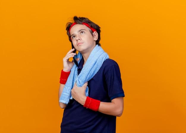 Junger hübscher sportlicher junge, der stirnband und armbänder mit zahnspangen und handtuch um hals ergreift, handtuch, das am telefon spricht, lokalisiert auf orange hintergrund mit kopienraum