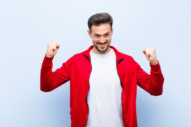Junger hübscher sportmann oder -monitor, die glücklich, positiv und erfolgreich sich fühlen und sieg, leistungen oder viel glück gegen flache wand feiern