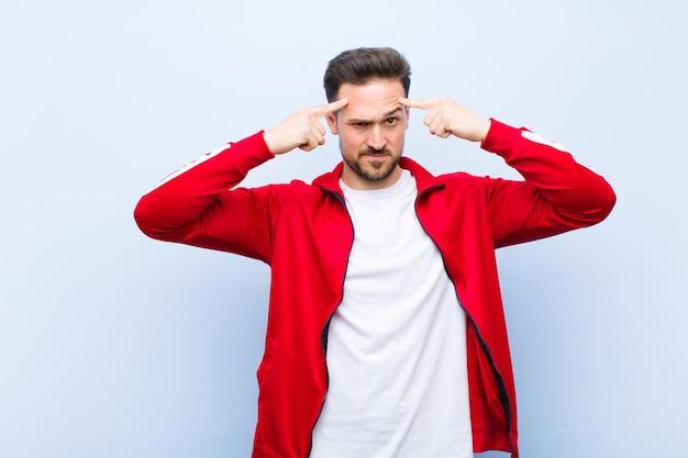 Junger hübscher sportmann oder -monitor mit einem ernsten und starken blick, brainstorming und denken an ein schwieriges problem gegen flache wand