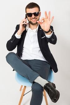 Junger hübscher stilvoller hipster-mann in der schwarzen jacke, geschäftsart, weißes hemd, isoliert, entspannt auf bürostuhl sitzend, auf smartphone sprechend, lächelnd, glücklich, positiv, sonnenbrille