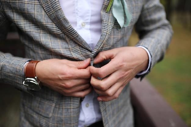 Junger hübscher stilvoller mann gekleidet in der modernen formalen kleidung, die jacke zuknöpft. nahaufnahme der hände des kerls in der grauen jacke, im violetten hemd. person bereit für hochzeitsfeier oder abschlussfeier.