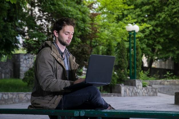 Junger hübscher student, der auf einer holzbank im park mit laptop-computer sitzt.