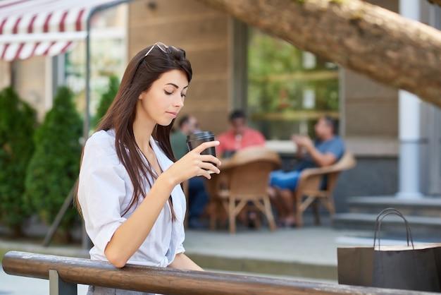 Junger hübscher student, der auf papierschale mit dem kaffee, sitzend auf holzbank schaut.