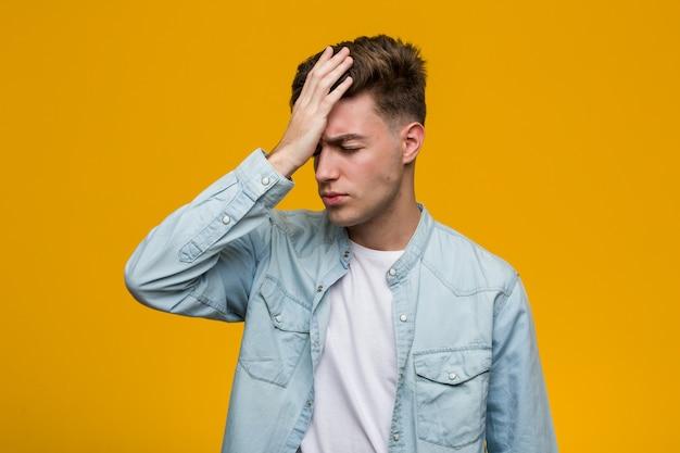 Junger hübscher student, der ein denimhemd vergisst etwas trägt, stirn mit palme schlägt und augen schließt.