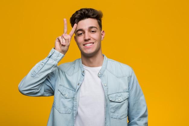Junger hübscher student, der ein denimhemd zeigt siegeszeichen und breit lächelt trägt