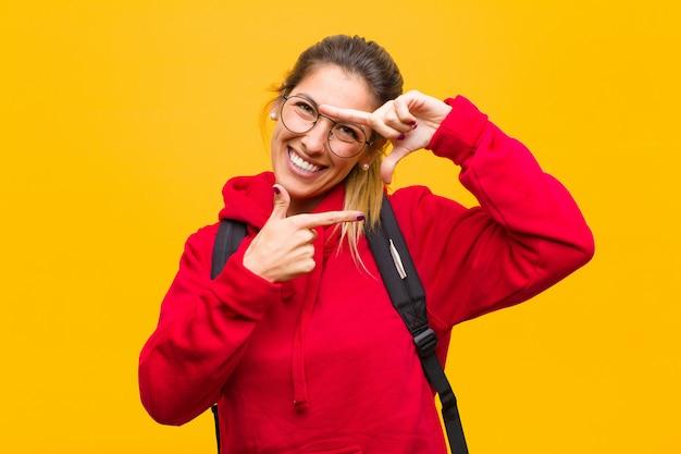 Junger hübscher student, der glücklich, freundlich und positiv sich fühlt, ein porträt oder einen fotorahmen mit den händen lächelt und macht